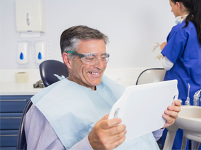 A middle-aged male patient admiring his smile in the mirror after receiving a dental bridge
