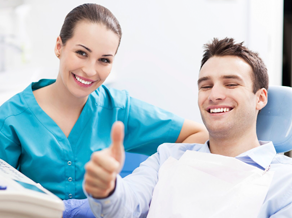A young male patient smiling and making a thumbs up symbol in the dental chair as a female hygienist treats him