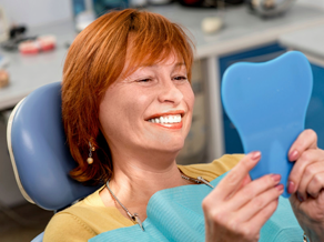 A middle-aged female patient admiring her smile in the mirror after a periodontal treatment