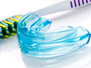 A protective mouth guard sitting next to a toothbrush