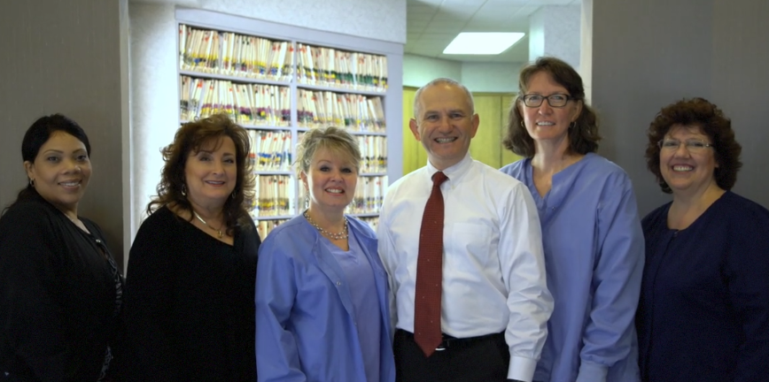 A group shot of Dr. Roman Shlafer and his dental team